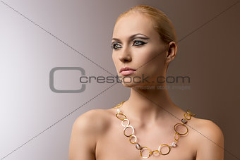 blonde girl with necklace looks at right