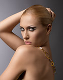blonde girl with necklace lookd in to the lens