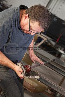 Artist Rolling Hot Glass Piece