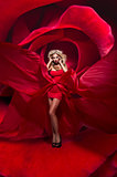 Beautiful young lady in red dress stands on flower rose