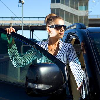 woman in black sunglasses near car