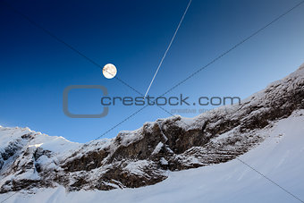 Full Moon and Airplane Trail in Blue Sky above Mountain Peak, Fr