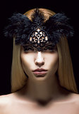 Beautiful Genuine Woman in Styled Black Mask with Feathers. Aristocratic Face