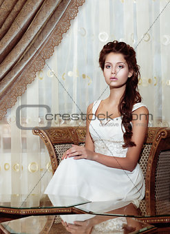 Femininity. Brown Hair Woman Bride in Wedding Dress sitting. Classic Romantic Interior