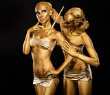Body Art. Woman painting Body with Paint Brush in Golden Color. Gold Make Up