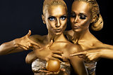 Masquerade. Enjoyment. Two Glossy Women with Golden Body Art. Glamor