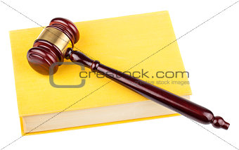 Wooden gavel on yellow book