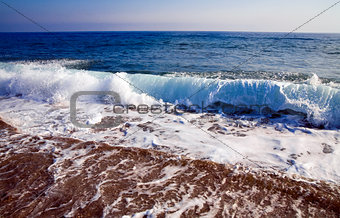 foamy shore blue waves over the horizon in a clear summer day