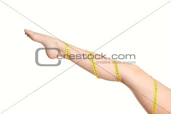 Beautiful woman leg with a coiled measure tape
