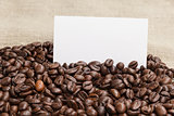 heap of coffee beans on burlap with card