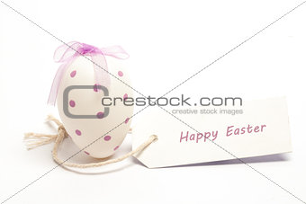 Easter egg with tag spelling out Happy easter