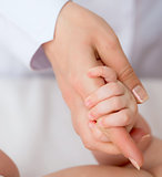 baby's hand with mother's finger