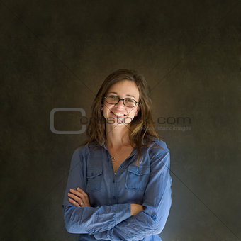 Business woman or teacher with glasses against a dark blackboard background
