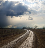 dramatic sky over field with dirty road
