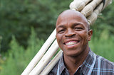 Stock photograph of a smiling black South African entrepreneur small business broom salesman