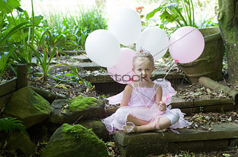 Little girl dressing up as a fairy-tale ballet princess on her birthday in forest garden