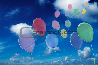 colored ballons against cloudy sky