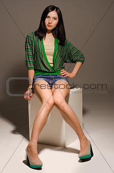 Beautiful long-legged young woman posing sitting