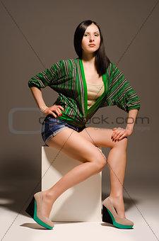 Beautiful sexy young woman posing sitting