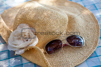 Concept of summer with straw hat and sunglasses on blue table