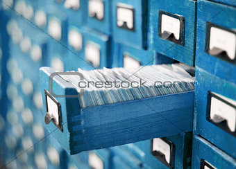 blue card catalog or cabinet with opened drawer and files