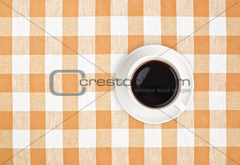 Top view of black coffee cup on brown checked tablecloth