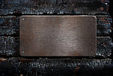 metal plate over burned wooden background