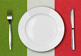 White plate, fork and knife top view on italian flag plastic tab