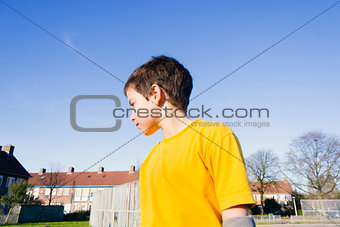Cute boy staying in the playground against blue sky
