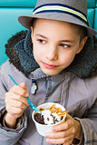 Cute teenage boy eating ice cream with chocolate topping
