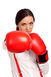 Portrait of business woman wearing boxing gloves