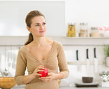 Portrait of thoughtful young woman with apple in modern kitchen