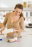 Happy young woman pouring milk into glass