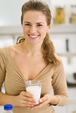 Portrait of happy young woman with glass of milk in kitchen