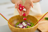 Closeup on housewife adding radishes into vegetable salad