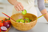 Closeup on housewife adding cucumber into vegetable salad