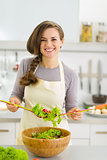 Happy young housewife mixing vegetable salad