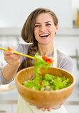 Happy young housewife giving spoon with vegetable salad