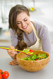 Happy young housewife with fresh vegetable salad in kitchen