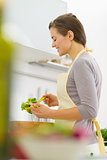 Happy young housewife mixing salad in modern kitchen