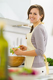 Smiling young housewife mixing salad in modern kitchen