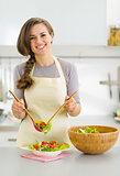 Happy young housewife served plate with fresh vegetable salad in