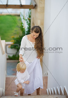 Mother and baby walking up stairs