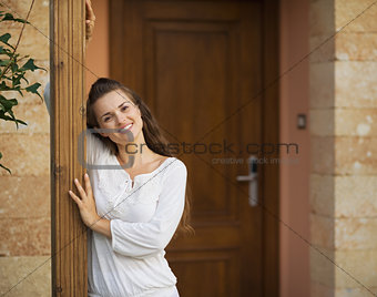 Portrait of happy young woman at doorstep