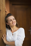 Happy young woman at doorstep looking on copy space