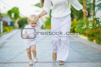 Mother and baby running outdoors
