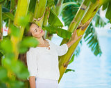 Relaxed young woman among tropical palms