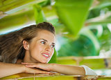 Happy young woman leaning on tropical palm and looking on copy s