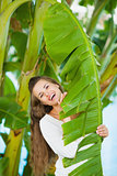 Portrait of smiling young woman among tropical palms