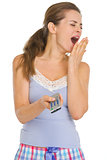 Young woman in pajamas with TV remote control yawing